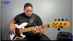 young black man sitting down playing a white bass guitar