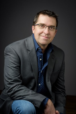 white male with brown hair and glasses dressed in jeans, a dark button down shirt and a grey blazer