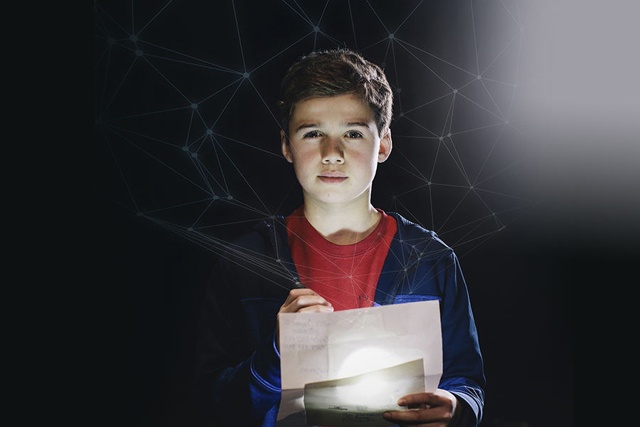 kid looking at paper with flashlight