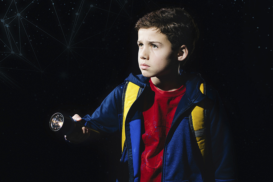 kid looking away with a flashlight