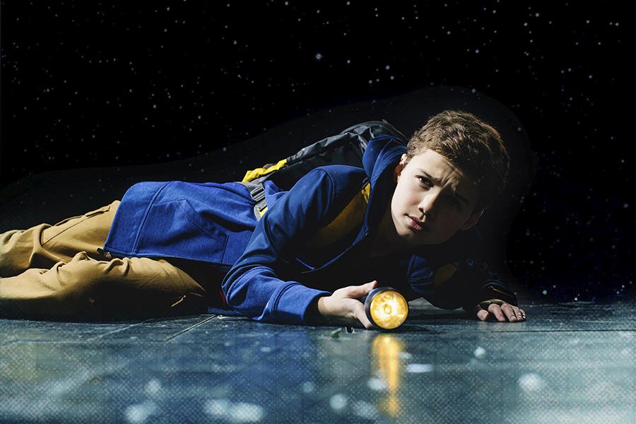 kid on floor looking with a flashlight