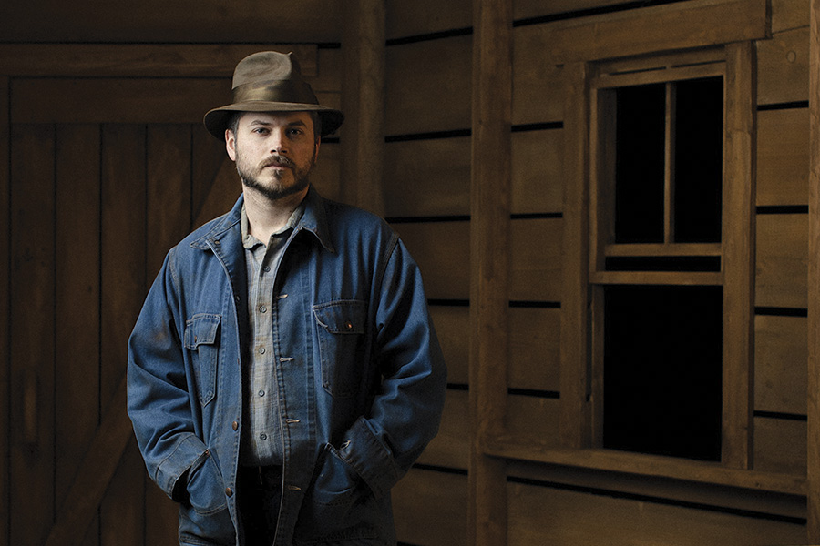 man standing in a barn in denim jacket and hat