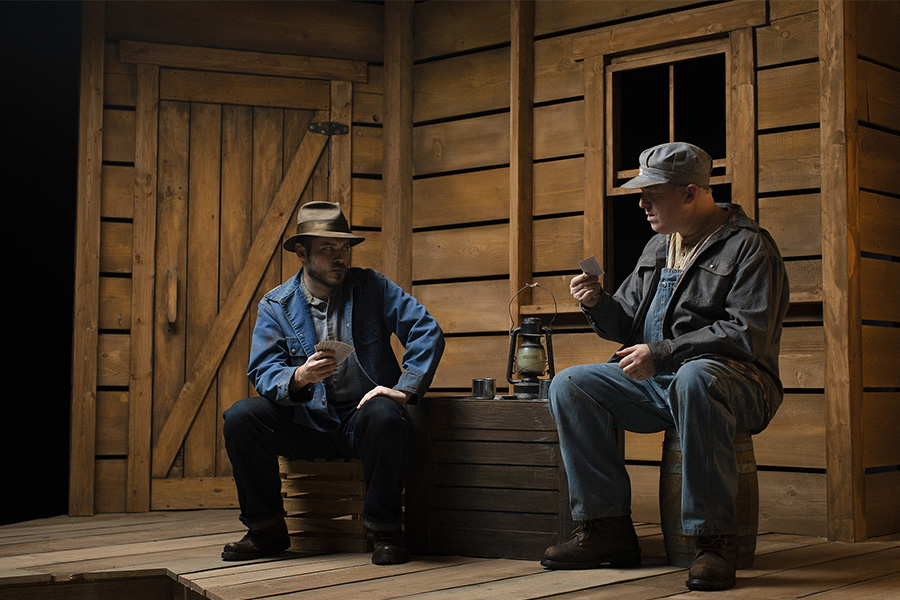 two men playing cards at a table in a wooden house / barn