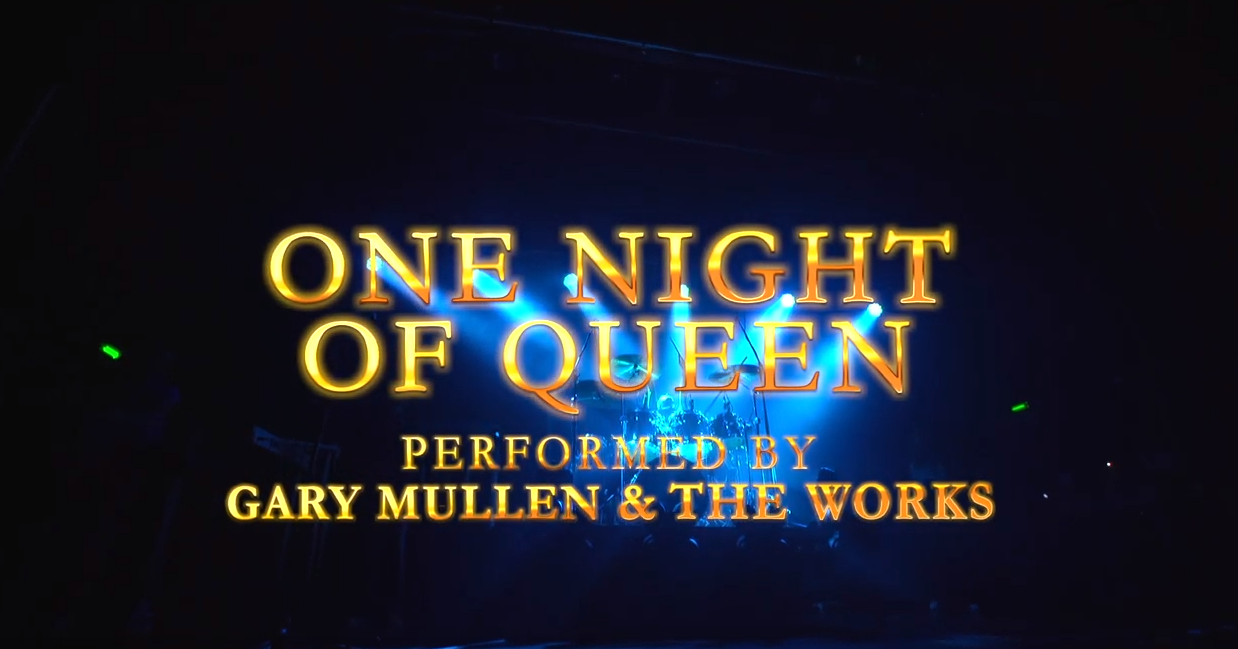 one night of queen text overlayed on a dark stage with a band performing