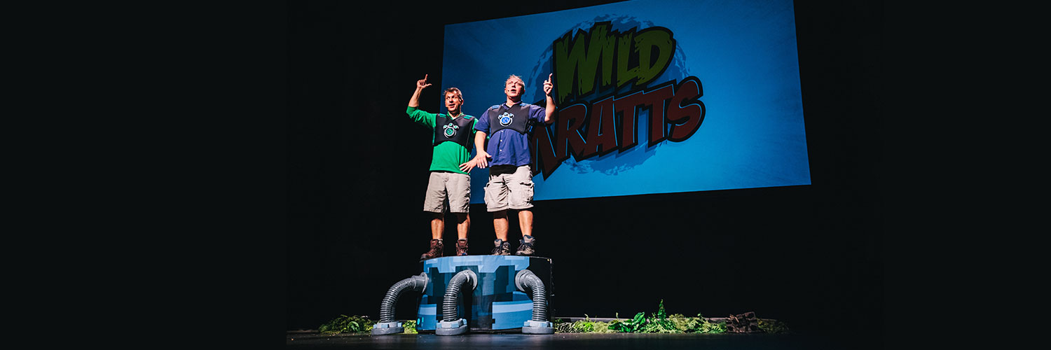 image of two men on stage dressed as wild kratt brothers